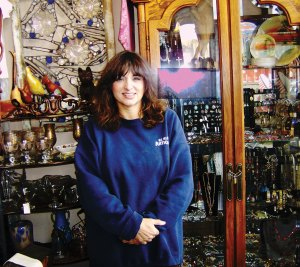 SUSAN WORTHY stands inside her internationally known antique store in downtown Huntington Beach, now a unique historical landmark. Photo OC Voice