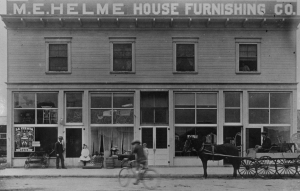 L-R: Mathew Helme, daughter Amy, son Paul (on bike), unknown boy, and son Barney Helme on the wagon (1907). The original building shown here is being restored. Photo courtesy Susan Worthy.